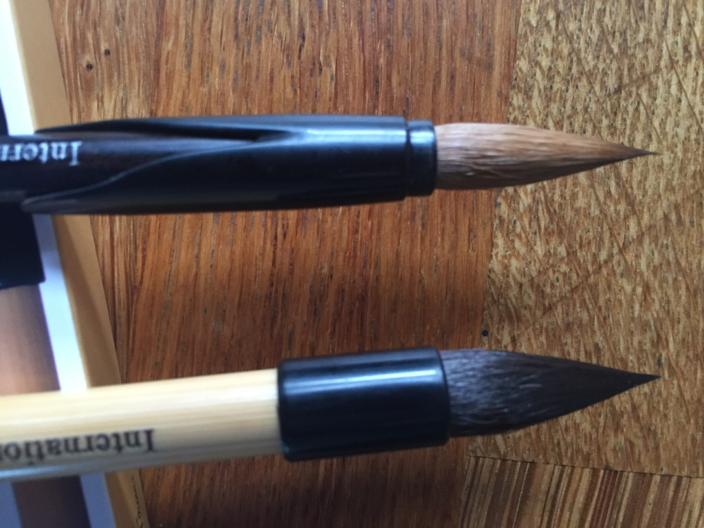 A photography of the surgically precise points of Ocean-i's Tulip watercolour brush, with it's inverted brush protector on the handle, and below it, the Piccolo watercolour brush
