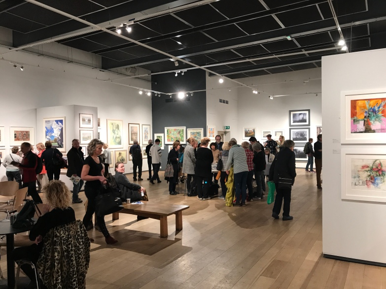 A photograph of the main gallery space at the Mall Galleries, with a huddle around David Poxon RI in the middle of the room.