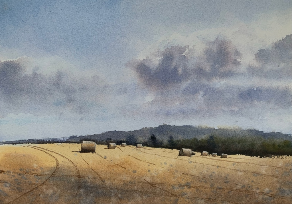 Watercolour painting of a Sussex field with hay bales and distant trees and hills in the background by artist John Haywood
